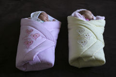 Baby twins in baby blankets. Ready for a walk on a dark background stock image
