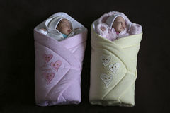 Baby twins in baby blankets. Ready for a walk on a dark background stock photography