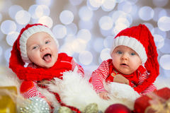 Baby twins in santa costumes Royalty Free Stock Photo