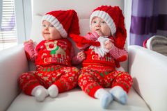 Baby twins in santa costumes Royalty Free Stock Image