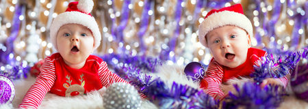 Baby twins in santa costumes for Christmas Royalty Free Stock Images
