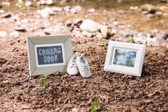 Baby Ultrasound and Coming Soon Photo Frames and Baby shoes. Baby Ultrasound and Coming Soon Photo Frames with Baby shoes in Forest royalty free stock photo