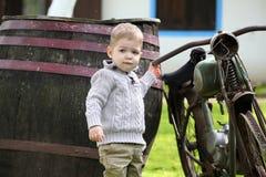 Baby um das alte Fahrrad Stockfotografie