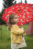 Baby with umbrella. Child play with red umbrella Royalty Free Stock Image