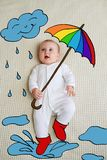 Baby with umbrella and rainfall concept. Cute baby girl with umbrella and rainfall concept on bed stock photo