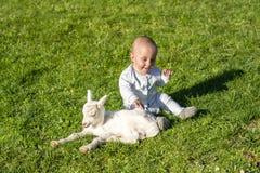 Baby und Goatling auf Frühlingsspiel zusammen Lizenzfreie Stockbilder