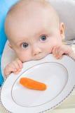 Baby und ihre erste Karotte Lizenzfreies Stockfoto