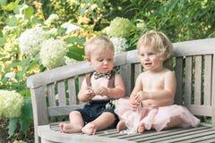 Baby und Junge, die auf Holzbank sitzen und auf Perle schauen lizenzfreie stockfotos