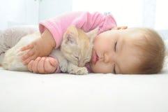 Baby und Katze, die zusammen schlafen Lizenzfreies Stockfoto