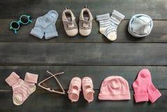 Baby und Mädchenschuhe und -socken auf blauem hölzernem Hintergrund lizenzfreies stockbild