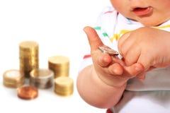 Baby und Münze. Stockbilder