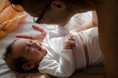 Baby und Mama, die an einander umfassen und lächeln stockfotos