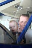 Baby und Mann, die in der Windschutzscheibe des antiken Flugzeuges lächeln Lizenzfreies Stockbild