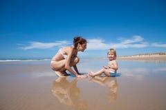 Baby und Mutter, die an der Küste sitzen Lizenzfreie Stockbilder