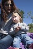 Baby und Mutter, die im Park essen Stockbilder
