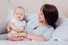 Baby und Mutter in ihren Pyjamas, die in einer guten Laune auf dem Bett spielen, lizenzfreie stockbilder