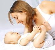 Baby und Mutter im Bett Lizenzfreie Stockfotografie
