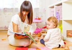 Baby und Mutter mit Bilderbuch Lizenzfreie Stockfotos