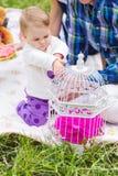 Baby und Mutter und Vater, die auf dem grünen Gras, Familienpicknick spielen stockfotografie
