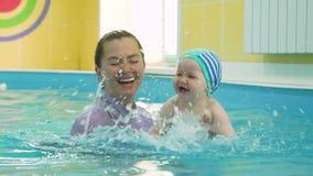 Baby und schwimmender Lehrer Having Fun in einem Pool stock footage