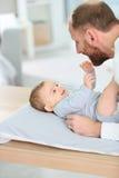 Baby und sein Vater, die auf changint Tabelle spielen Lizenzfreies Stockfoto