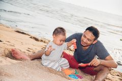 Baby- und Vatervati, der Spaß auf Sandstrand spielt stockbilder