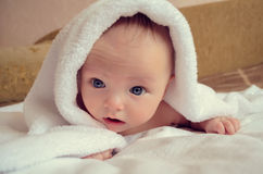 Baby under blanket with big blue eyes Royalty Free Stock Photos