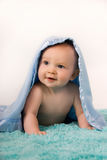Baby under a blue blanket. Cute little boy baby under a blue blanket with an adorable expression on his face Stock Photo
