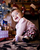 Baby Under Christmas Tree. A baby smiling under the Christmas tree Royalty Free Stock Photo