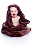 Baby under towel. A beautiful baby under a brown towel Royalty Free Stock Photography