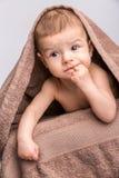 Baby under towel Stock Photos