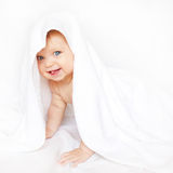 Baby under the towel showing tongue. Stock Image