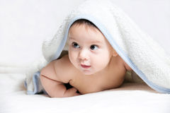 Baby under white towel Stock Photography