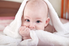 Baby under white towel Stock Photo