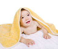 Baby under yellow towel looking up Stock Image