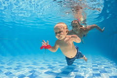 Baby underwater swimming lesson with instructor in the pool Royalty Free Stock Image