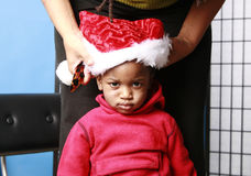 Baby unhappily being fitted with a Santa hat Royalty Free Stock Photos