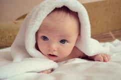 Baby unter Decke mit großen blauen Augen Lizenzfreie Stockfotos