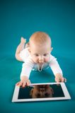 Baby using digital tablet. Baby girl on blue background Stock Image