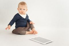 Baby using digital tablet on white Stock Image