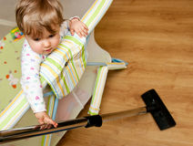 Baby with vacuum cleaner. Baby girl in cot holding vacuum cleaner Royalty Free Stock Image