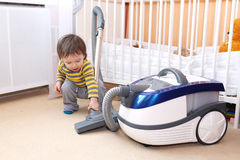 Baby with vacuum cleaner Stock Photography
