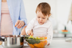 Baby with vegetables and mother cooking at home. Family, food, healthy eating, cooking and people concept - happy mother and little baby girl with vegetables and Royalty Free Stock Photography