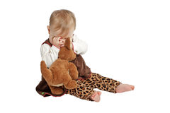 Baby in velvet dress plays peekaboo with toy Royalty Free Stock Photography