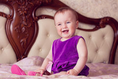 Baby in violet dress and pink shoes laughs Stock Image