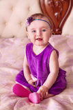 Baby in violet dress and pink shoes smiling Royalty Free Stock Image