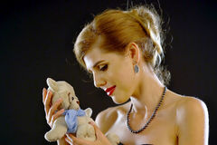 Baby waiting of young woman. Dreaming of children for adoption . Portrait of nude shoulders girl hugged her bear toys. Mom cuddle his first toy. Backlight Royalty Free Stock Image