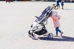 baby walk with carriage on street royalty free stock images