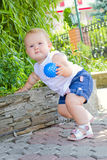 Baby on a walk. Child walking in a green park with a ball in his hand stock photos