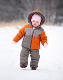 Baby walk by snow road in park. Cute baby walk by snow road near winter park Stock Image
